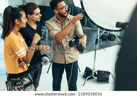 Photographer explaining about the shot to his team in the studio. Photographer talking to his assistants holding a camera during a photo shoot.