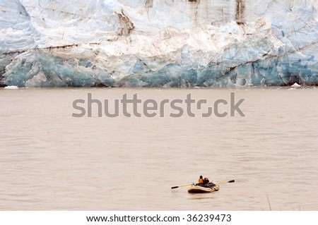 photographer floating by glacier
