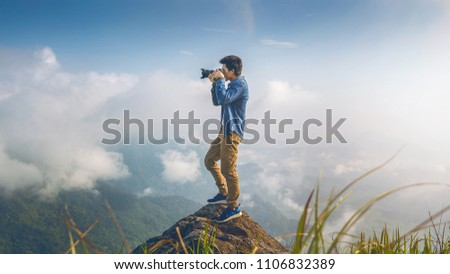 Photographer hand holding camera and standing on top of the rock in nature. Travel concept. Vintage tone.