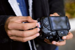 Photographer hand holds Memory card - Flash card near professional DSLR camera. Male photographer ready to insert memory card to his photo camera