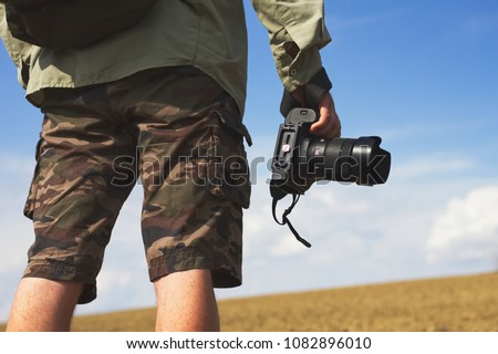 Photographer holding a camera outdoors. Man wearing camouflage shorts taking pictures of nature.