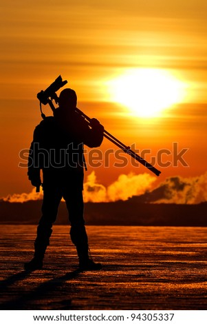 Photographer holding a tripod and camera at the sunrise on a frozen lake, silhouette