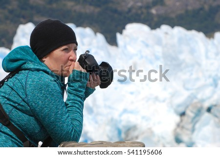 Photographer holding camera looking in awe at Perito Moreno Glacier in Los Glaciares National Park, Argentina.