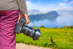 Photographer holds her DSLR camera at beautiful nature view on Mount Rigi with Lake Lucerne and snow-capped mountain in background