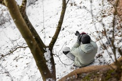 photographer holds his camera and taking pictures of winter landscape
