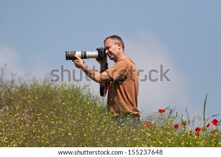 Photographer in action in poppy field
