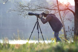 Photographer in action with telephoto lens at morning light
