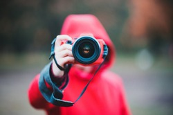 Photographer in center taking photo with lens and red hoodie rainy autumn day