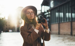 Photographer in glasses with retro camera take photo in city. Tourist smiling girl in hat travels in Barcelona holiday. Sunlight flare street in europe. Traveler hipster shoot sun day