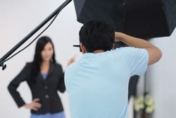 photographer is taking pictures with a digital camera with asian model in studio. Photography in action work with model wearing uniform. Selective focus.