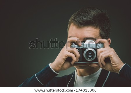 photographer looking through the lens of old film camera - stock photo