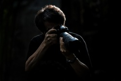 Photographer man person in action with camera and watch low key light isolated dark on black background.