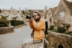 Photographer man taking photos in the village in Cotswolds, UK
