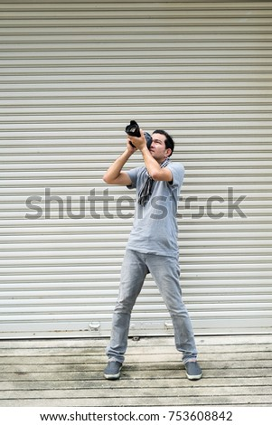 Photographer  man young shooting have fun on steel sheets background. #753608842