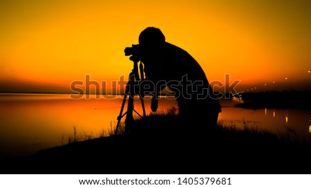 Photographer men are shooting the sunset to get beautiful pictures and use images as wallpaper background texture sunset shooting on the beach with a DSLR camera