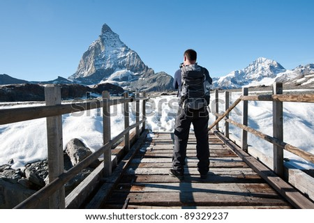 photographer on Glacier trail taking picture of Matterhorn, Switzerland