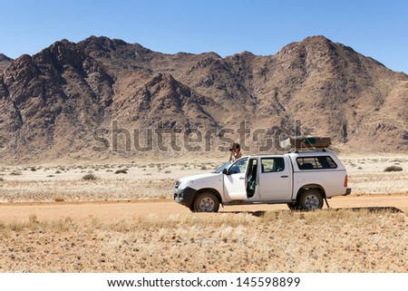 photographer on safari in Africa on his car