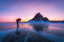 Photographer or Traveller using a professional DSLR camera take photo beautiful landscape of Baikal lake at sunset winter. The most famous tourist attraction in Rusia - Recreation and outdoor travel c