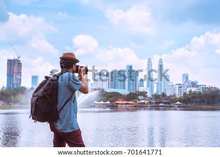 Photographer or Traveller using a professional DSLR camera take photo beautiful landscape of Kuala Lumpur skyscraper at Titiwangsa park Kualalumpur city, Malaysia.