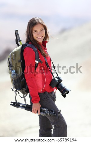 Photographer outdoors in nature taking pictures during hiking trip on Teide, Tenerife, Canary Islands. Beautiful smiling Asian / Caucasian woman.