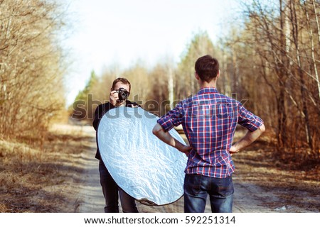 Photographer Photographing Male Model in Forest. Backstage of Fashion Photoshoot by Professional Photographer with DSLR Camera and Reflector