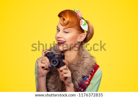 Photographer. Portrait head shot young woman lady pinup girl smiling taking pictures holding dslr camera winking blinking eye isolated yellow background Photography hobby paparazzi Vintage retro style