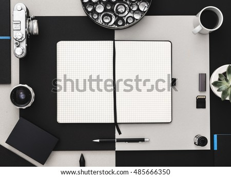 Photographer's desk with scrapbook, vintage camera and coffee in black and grey. Flat lay. Modern and elegant.