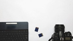 Photographer's workplace on a white background. Modern laptop, digital camera, memory card. Top view. Copy space. Equipment for the photographer. The concept of freelancing
