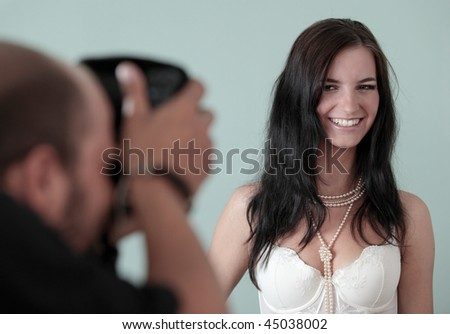 Photographer shooting a female photo model in a studio