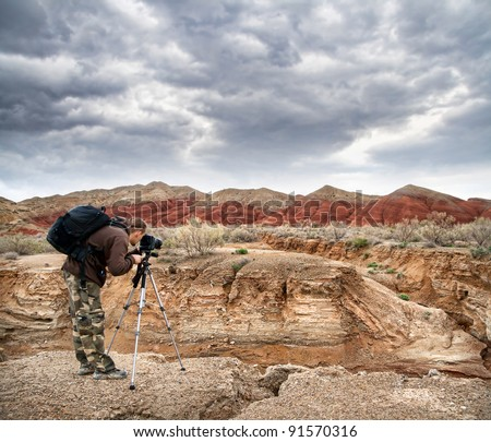 Photographer shooting drought Aktau mountains at dramatic sky background in altyn emel national park in Kazakhstan