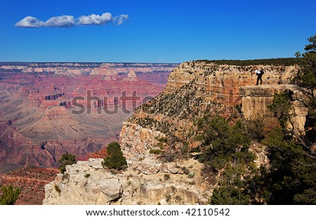 Photographer shooting the Grand Canyon at the edge of the south rim, Arizona