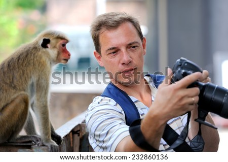 Photographer shows a monkey by her photo shoot