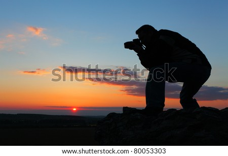 Photographer silhouette in outdoor with dramatic sunset.