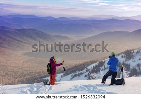 photographer skier shoots on camera girl snowboarder taking a selfie on the phone, high in the mountains on the background of the valley. Skiers in winter nature. Selfie photo. Sunset, edit space #1526332094