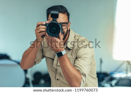 Photographer standing in position to take a photograph. Man looking into a digital camera for taking  a photograph. #1199760073