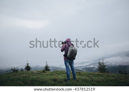 Photographer standing on the top of the mountain and make a photo of the landscape