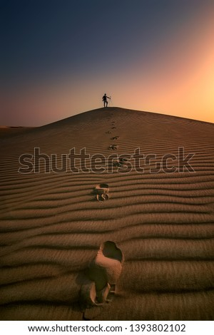 Photographer stands alone in the Desert leaving food steps in Dammam Saudi Arabia. Beautiful Sunrise background with sand dune structure,