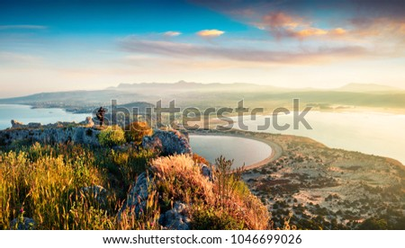 Photographer take a picture of spring view of the Voidokilia beach from Navarino Castle. Great sunrise on the Ionian Sea, Pylos town location, Peloponnese, Greece, Europe.