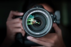 photographer  take pictures Snapshot with camera. man hand holding with camera looking through lens.Concept for photographing articles Professionally