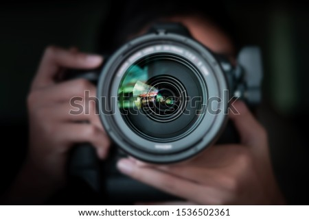 Photo of  photographer  take pictures Snapshot with camera. man hand holding with camera looking through lens.Concept for photographing articles Professionally