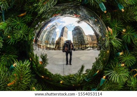 Photographer takes a photo of a self reflection on a holiday tree ornament.