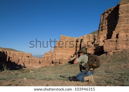 Photographer takes pictures sitting in picturesque canyon