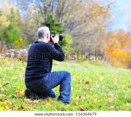 Photographer taking a picture of the beautiful fall scenery