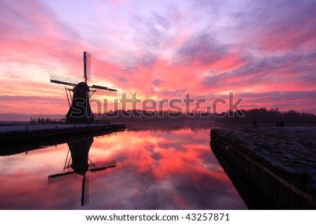 Photographer taking a shot of silhouette of Dutch windmill during a cold sunset in winter.