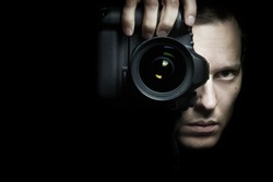 Photographer taking photo with camera on black background