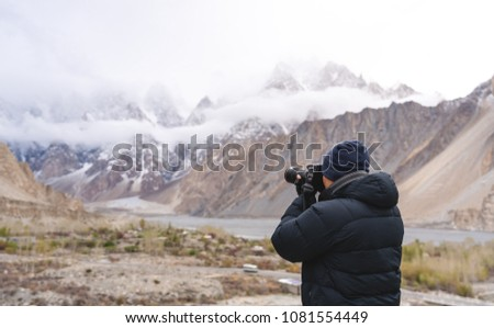 Photographer taking photograph of mountain landscape by dslr camera