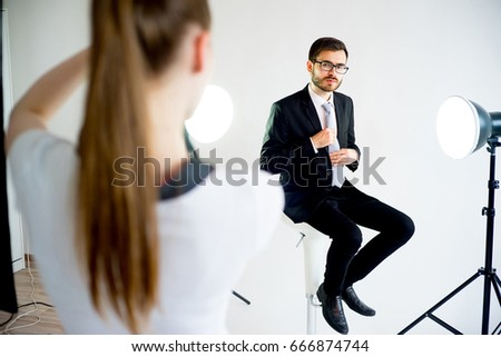 Photographer Taking Picture Of A Model In Studio 666874744