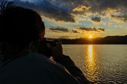 Photographer taking picture of the beautiful sunset landscape around Lake Windermere at Ambelside, United Kingdom