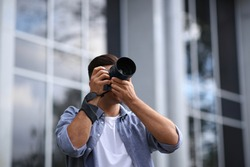 Photographer taking picture with professional camera on city street