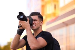 Photographer taking picture with professional camera on city street at sunset